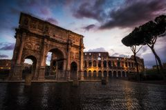 Colosseum and Constantine Arch at Night Stock Photo