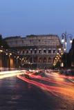 Colosseum e carros na noite, Roma Foto de Stock