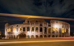 Colosseum en Lichte Stroken in Nacht stock foto's