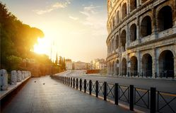 Colosseum in the morning. Colosseum and road at morning sunlight in Rome, Italy Royalty Free Stock Image