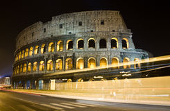 Colosseum at Night. Long exposure shot of Colosseum with the movement of the bus in the foreground Stock Photos