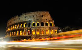 Colosseum by Night. The Colosseum viewed from the Via dei Fori Imperiali as many cars are leaving light streaks on winter evening stock images