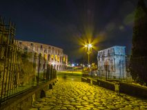 Colosseum by night. Night view of the Colosseum and the Arch of Constantine from the Via Sacra. In Rome, Italy. Long exposure Stock Photography