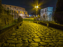 Colosseum by night. Night view of the Colosseum and the Arch of Constantine from the Via Sacra. In Rome, Italy. Long exposure Royalty Free Stock Images