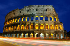 The Colosseum, Rome, Italy. The Colosseum at dusk with traffic moving past it creating streaks of light Royalty Free Stock Image