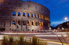 The Colosseum in Rome, Italy at night with traffic streaking pas royalty free stock photography