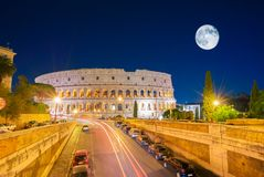 Colosseum in Rome, Italy. View of Colosseum illuminated at nigh with traffic lights and moon in Rome, Italy royalty free stock image
