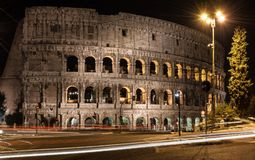 Colosseum in Rome at night. Rome colosseum at night with traffic car trail light, a street lamp and a tree Stock Photo