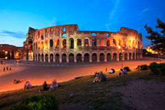 The Colosseum in Rome by night (at twilight). The Colloseo in Rome at twilight. Couples sii One of the most known landmark of Italy. Couples are sitting on the Stock Photo