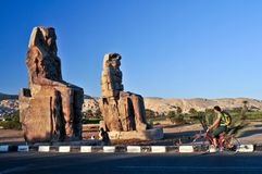 The Colossi of Memnon. At dusk, and a cyclist passing. Luxor, Egypt Royalty Free Stock Photo