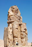 Colossi of Memnon in Egypt. Unidentify man sitting infront of Pharaoh Amenhotep III statue in Colossi of Memnon in Luxor, Egypt. Photo taken on February 26, 2007 Royalty Free Stock Photos