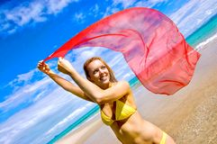Colour at the beach. Women in yellow bikini with red scarf at the waters edge basking in the sun ,  The sky is a royal blue and the ocean is crystal clear with Stock Images