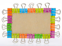 Colour binder clips frame round old paper. Isolated on white background Stock Image