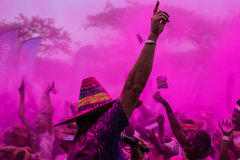 Colour Burst. A crowd goes wild for a DJ playing music at a Colour Run festival, with purple smoke filling the air Royalty Free Stock Image
