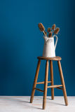 Colour Card and Vase on a Stool Over Blue Backdrop Stock Photography