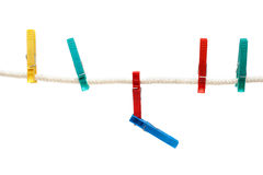 Colour clothes-pegs hung on linen rope Stock Photo