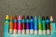 Colour crayons on a dark grey background. Twelve different Colour crayons on a dark grey background Royalty Free Stock Image