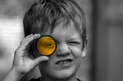 Boy looking through yellow filter Stock Photos