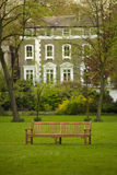 Colour home building with a bench. A wooden bench in a park with a grand colour house building in the background Stock Photos