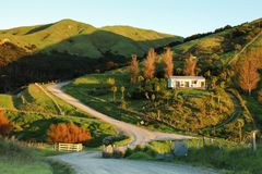 Picturesque rural house on a hill and rural road, Mahia Peninsula, New Zealand. Colour, horizontal image of picturesque rural road and house on a hill bathed in royalty free stock image