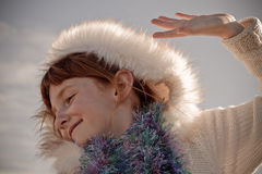 Colour landscape format image of young red haired girl wearing Eskimo styled fur trimmed hood. Colour landscape format image of young freckle faced red haired royalty free stock photos