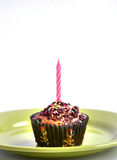 Colour muffin for kids party with candle at the top. Colour muffin for kids party with pink candle at the top Stock Photo