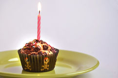 Colour muffin for kids party with pink candle at the top Royalty Free Stock Image