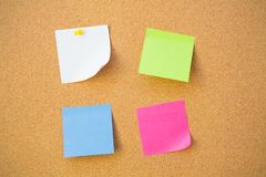 Colour note papers on pin board. Royalty Free Stock Image