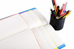 Colour notebooks and pen container Royalty Free Stock Photos