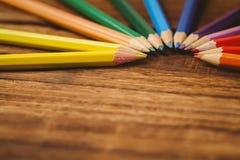 Colour ołówki na biurku w okręgu kształcie Zdjęcie Royalty Free