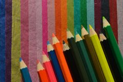 Colour ołówki na multicoloured tkankowego papieru tle obrazy stock