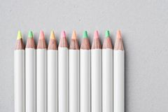 Colour pencils. Close-up of 10 colour pencils (of pastel coloured range) on a grey cardboard background Stock Photos