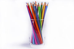 Colour pencils. Multicolour pencils in transparent glass in white background Royalty Free Stock Photo