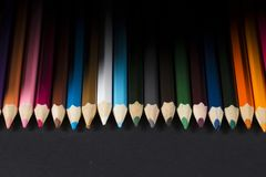 Colour pencils on black background. A row of colour pencils on a black background Stock Photography
