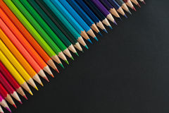 Colour pencils on black background Stock Images