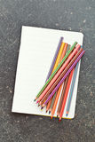 Colour pencils and blank workbook Royalty Free Stock Images