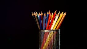Colour pencils in box isolated on black, rotation stock footage