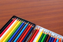Colour pencils on a brown wood table background. Close up Stock Photography