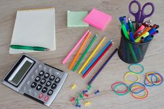 Colour pencils, calculator, notebook and office supplies, business accessories on wooden table Royalty Free Stock Photo
