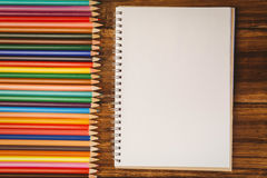 Colour pencils on desk with notepad Stock Photo