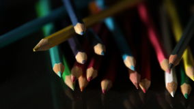Colour pencils falling on black surface stock footage