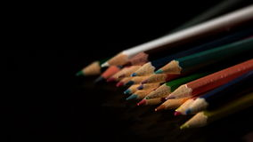 Colour pencils falling on black surface stock video footage