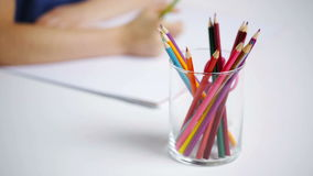 Colour pencils in glass and girl drawing on paper stock video