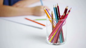 Colour pencils in glass and girl drawing on paper stock video footage