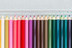 Colour pencils on grey paper box background Stock Image