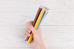 Colour Pencils in hand. On white wooden background Royalty Free Stock Image
