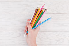 Colour Pencils in hand. On white wooden background Stock Image