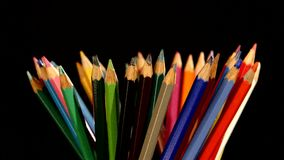 Colour pencils isolated on black, rotation stock video