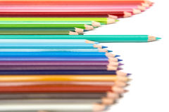 Colour Pencils. A single colour pencil deviating from a group of colour pencils lined up in a wave configuration Stock Photos