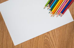 Colour pencils  on white paper and wooden background Stock Images